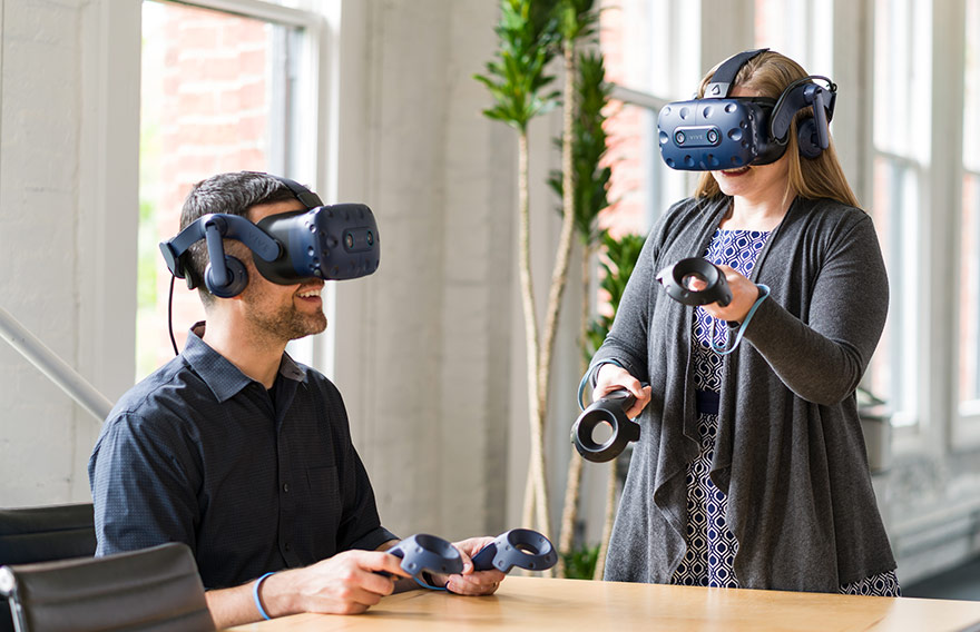 A man and woman using VIVE headsets in an office